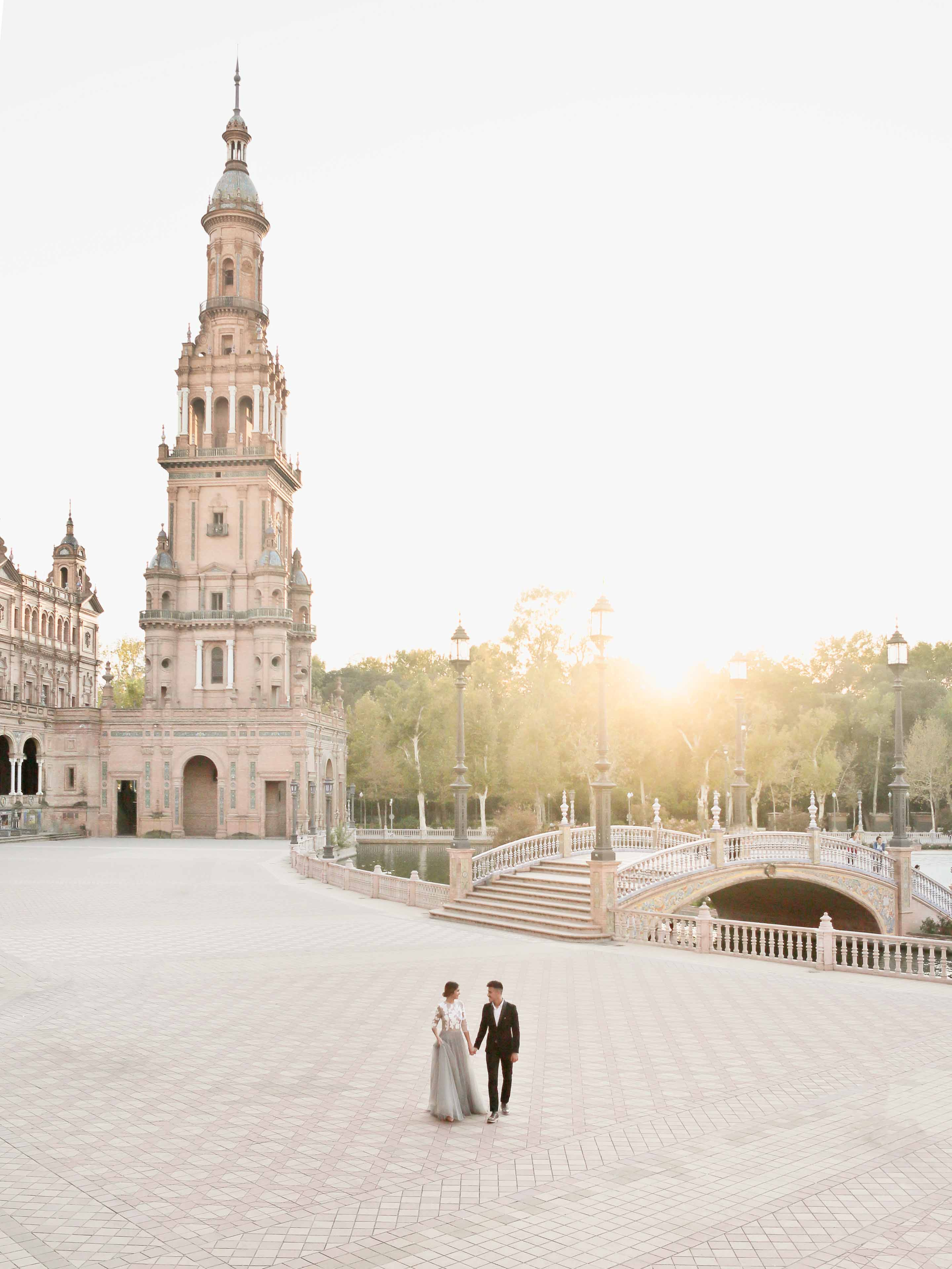 lovers strolling at sunset in the desert plaza de espana in seville