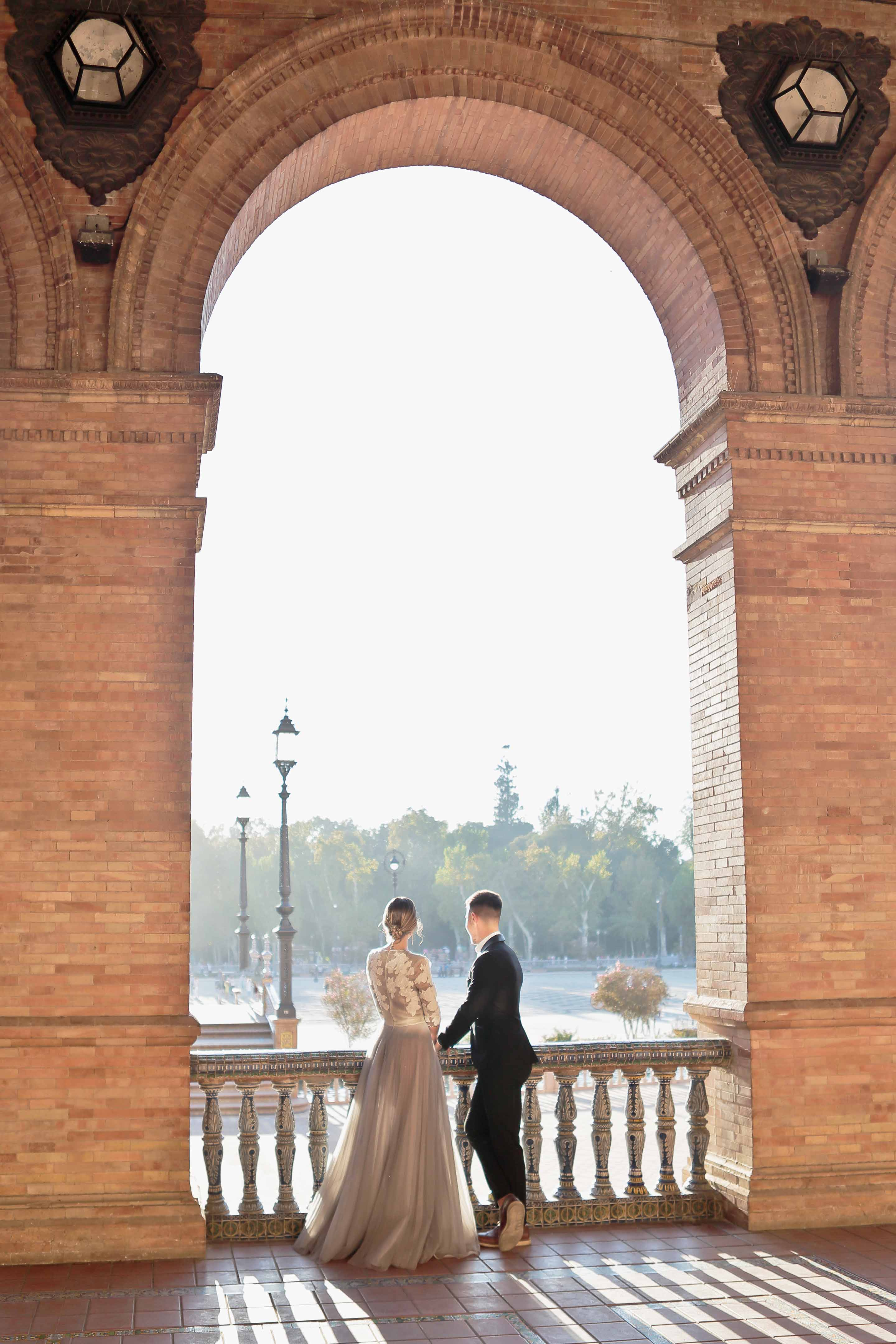 lovebirds stolling under the majestic arches of plaza de espana in seville