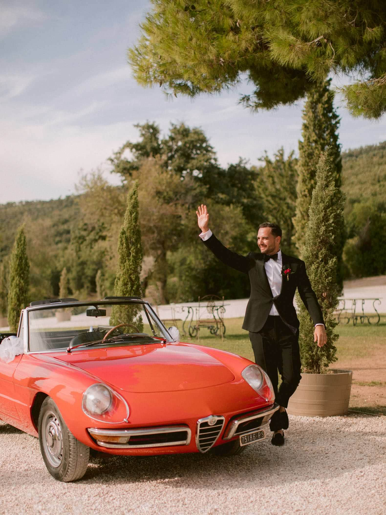 the groom arriving at the ceremony with a vintage italian car