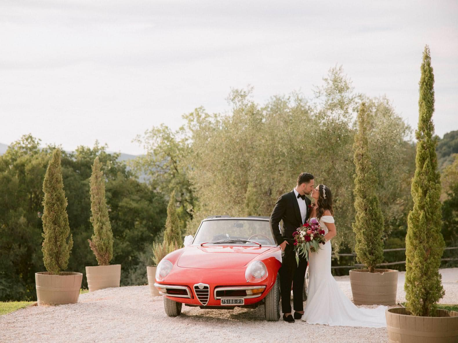 bride and groom kiss each other next to the vintage car