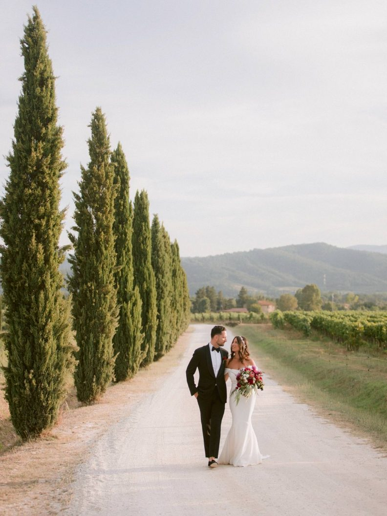 bride and groom walking in a dirt road of tuscany at sunset