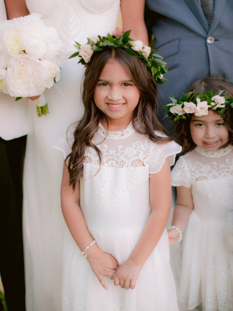 flower girl during family photos during the wedding