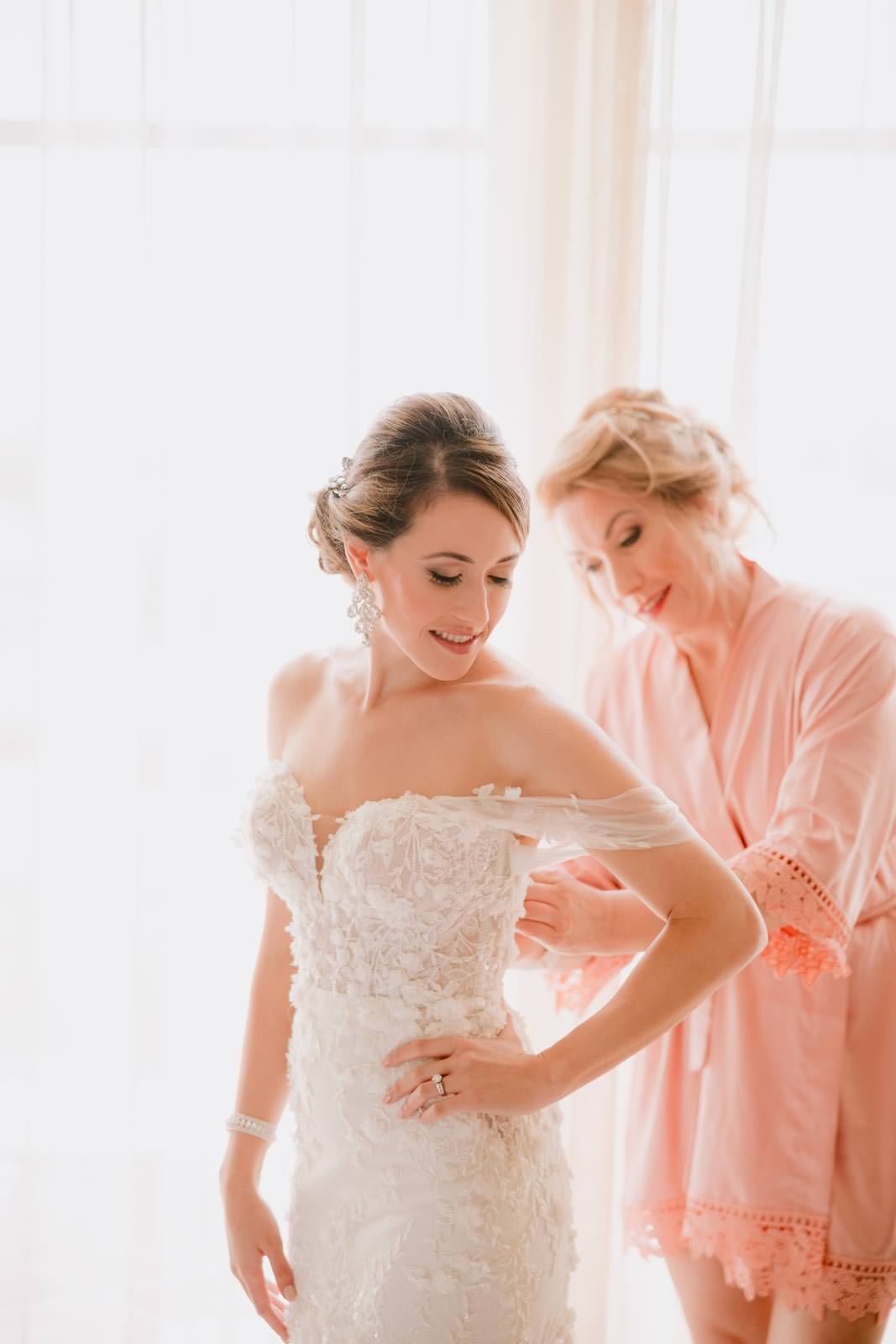 the bride is getting ready with her mother's help