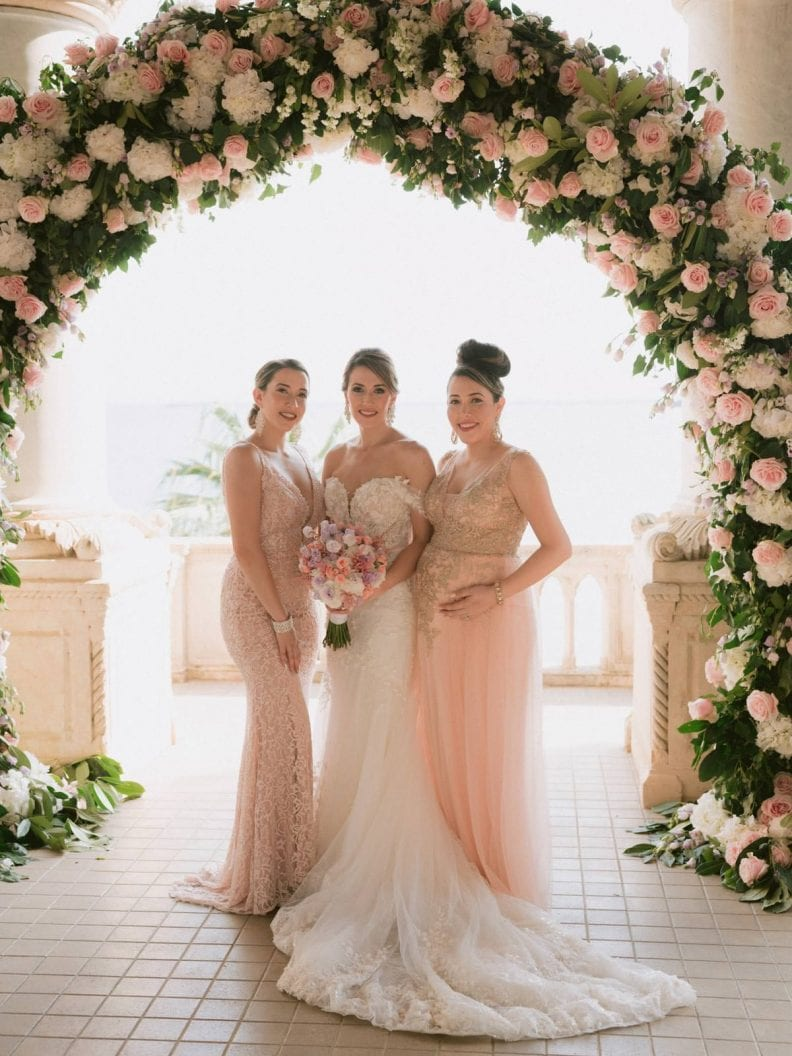 the bride and her sisters bridesmaids under the flower arch