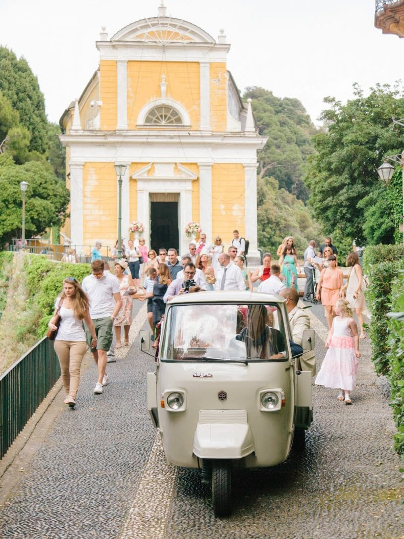 the newlywed are leaving the church in a vintage Piaggio Ape