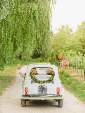 happy newlyweds in a fiat cinquecento