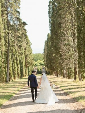 lovebirds walking on a road with cypresses