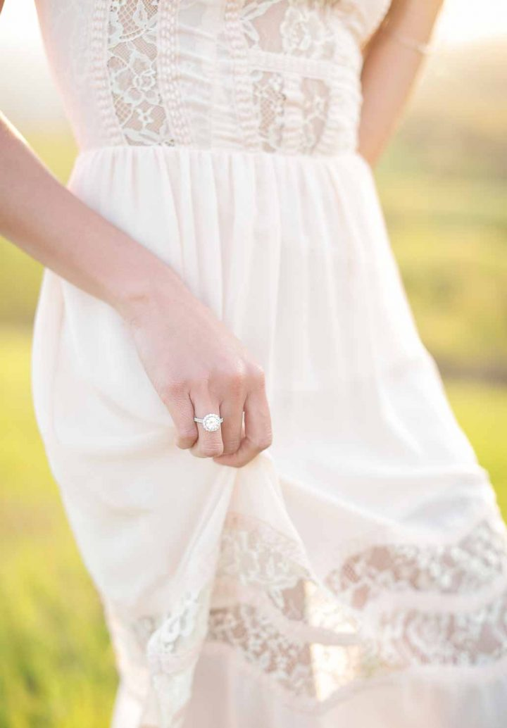 bride holding the dress with her hand and a ring