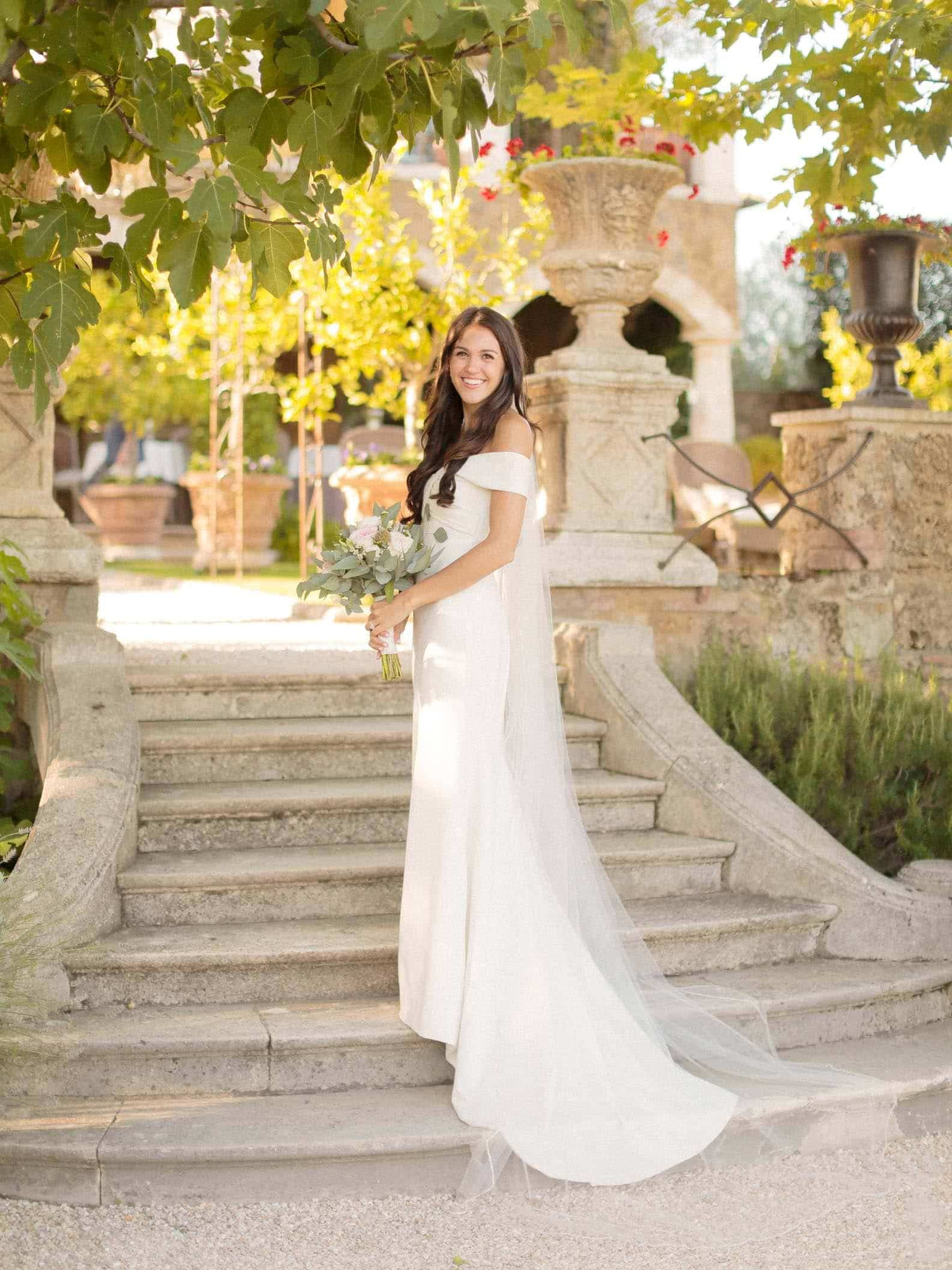 portrait of a pretty bride on the steps of the villa