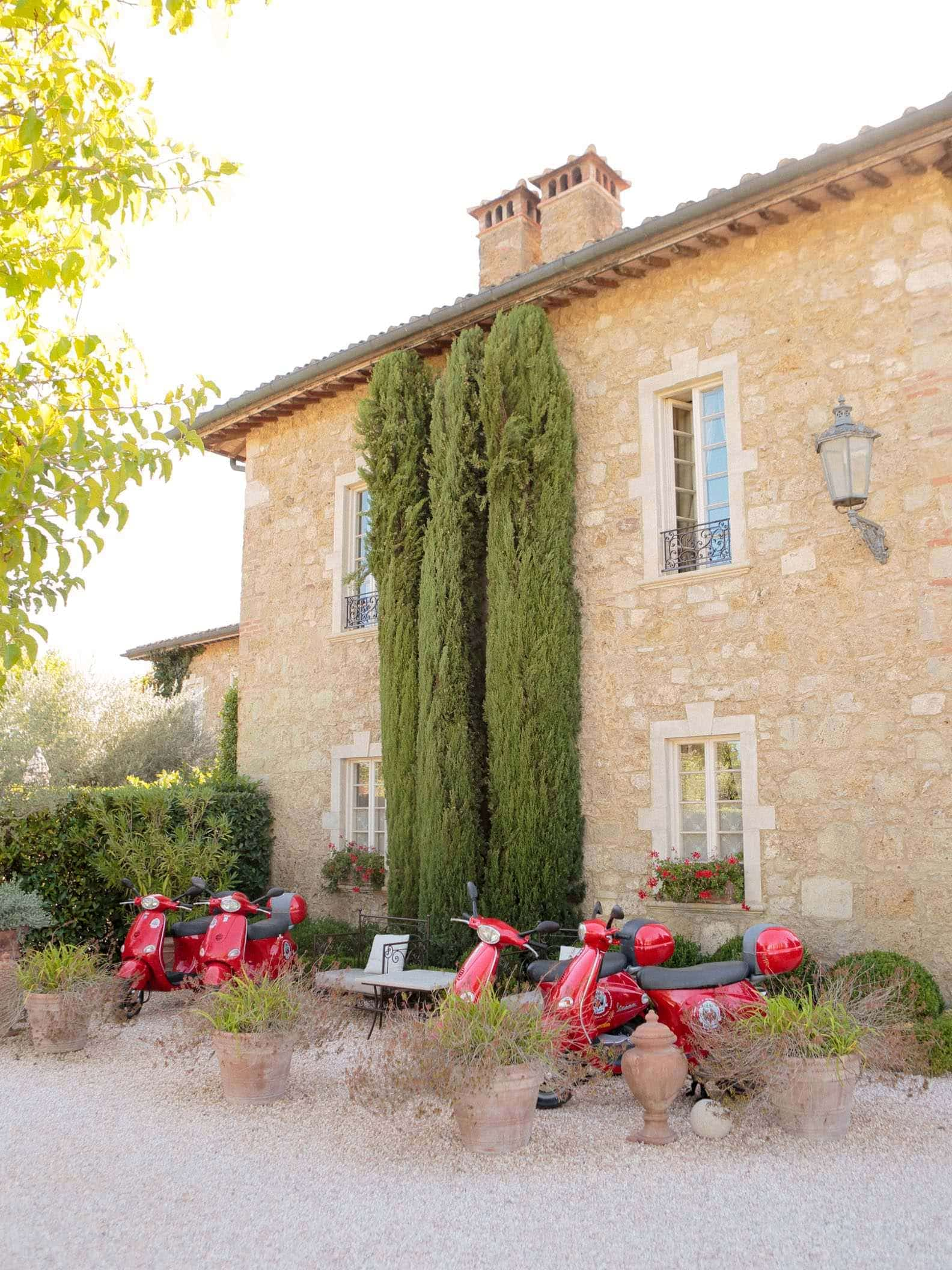 the wall if the main villa of borgo santo pietro, with cypress tress and red motorcycles