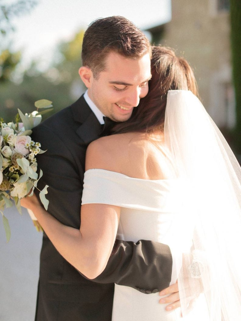 groom hugging the bride after seeing her with her dress on for the first time