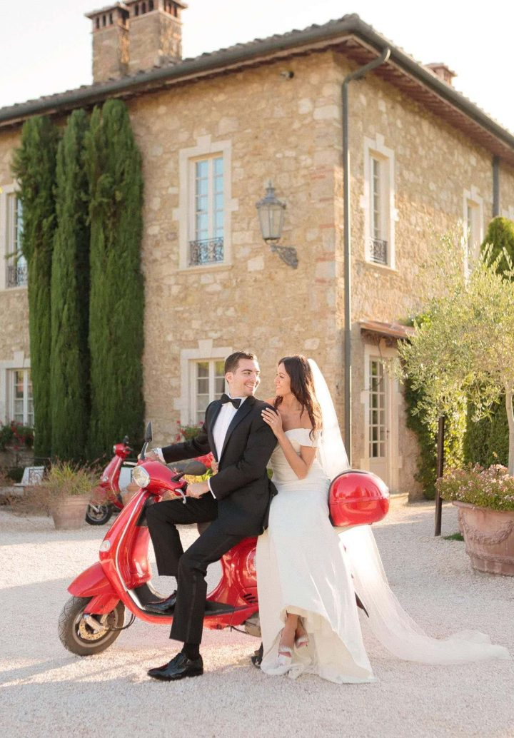 bride and groom happily looking at each other on a red italian motorcycle