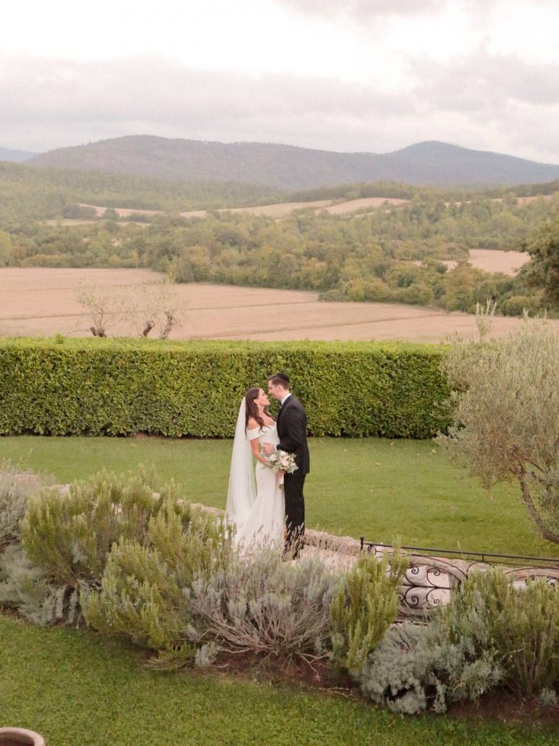 a kiss at dusk with tuscan countryside in the background