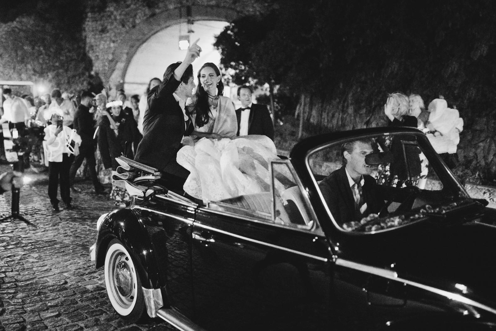 bride and groom leaving the reception with a vintage convertible car