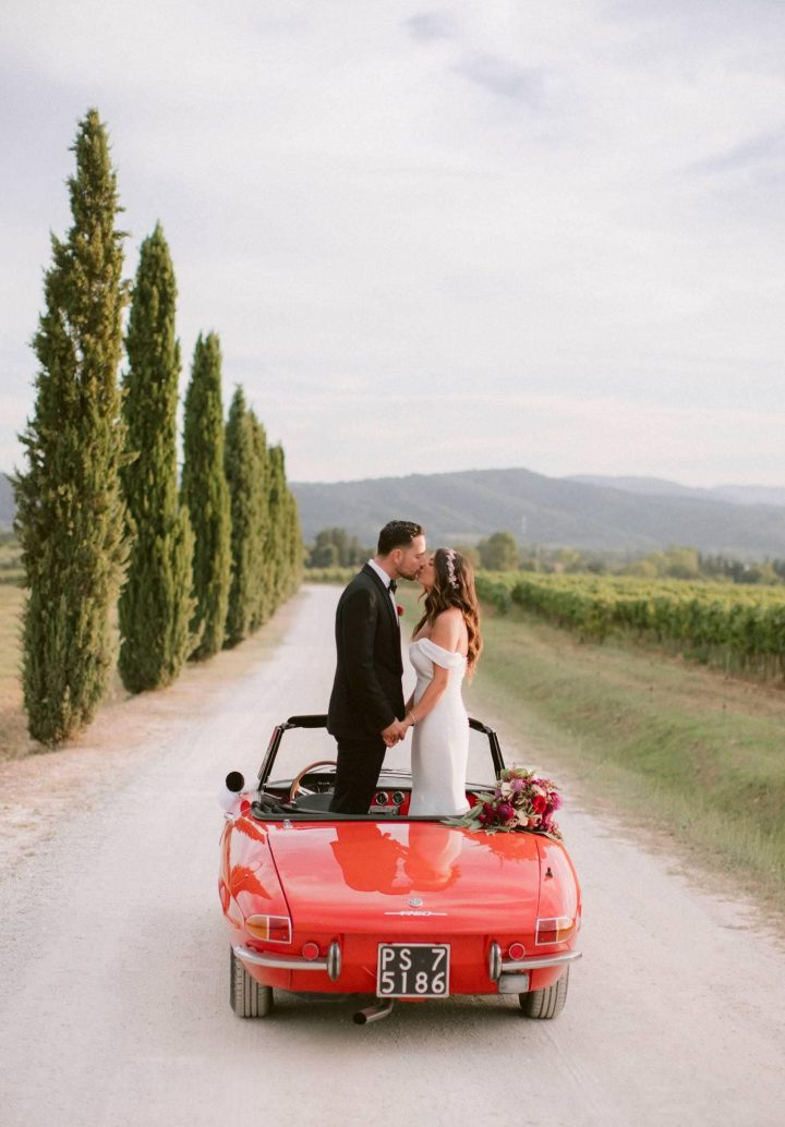 bride and groom on a vintage alfa romeo car