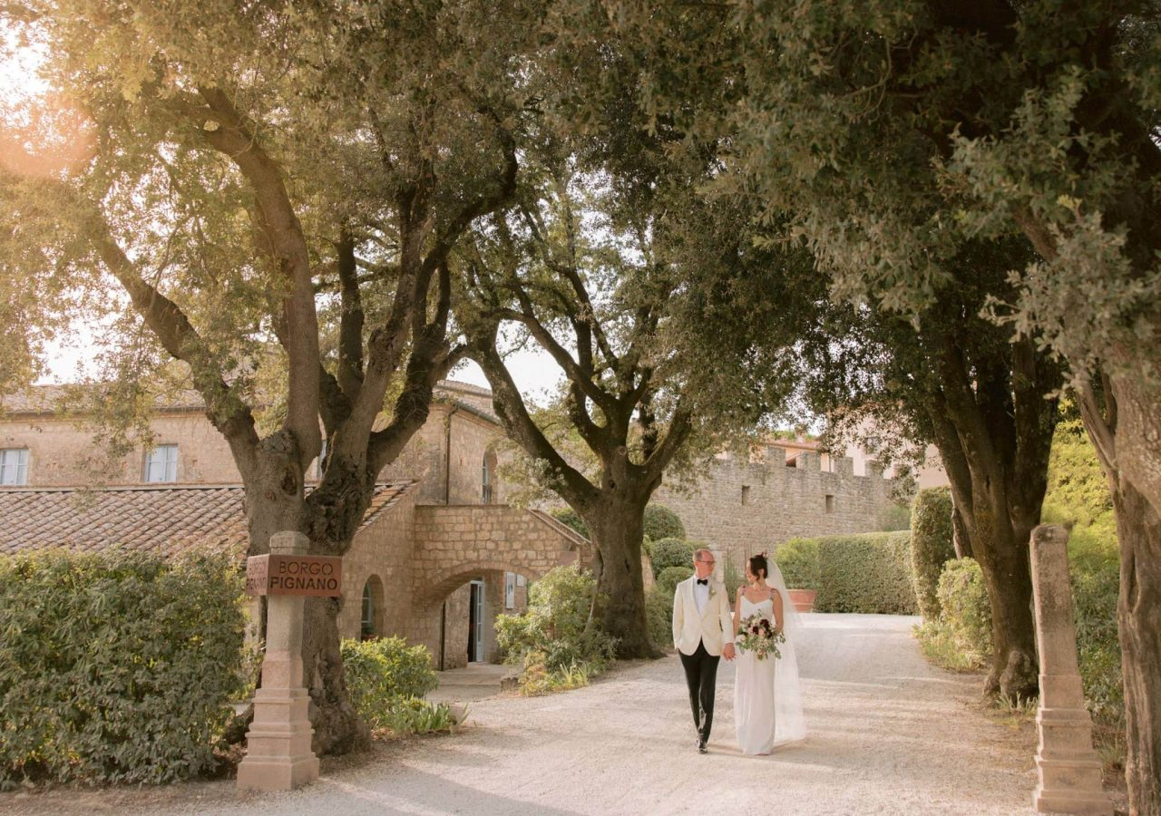 newlyweds walking happy in the property of borgo pignano at sunset