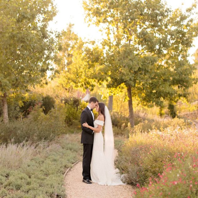 newlyweds posing for the photographer in the garden of borgo santo pietro in tuscany at sunset
